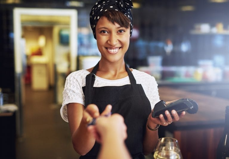 Smiling waitress taking a credit card